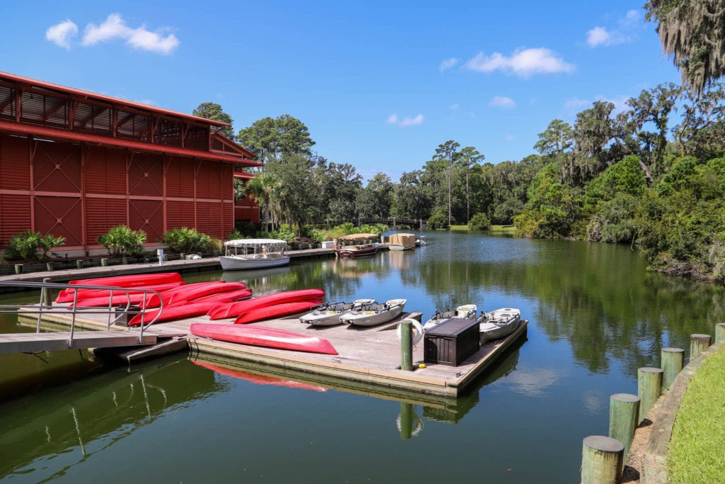 Body of water with dock holding red kayaks